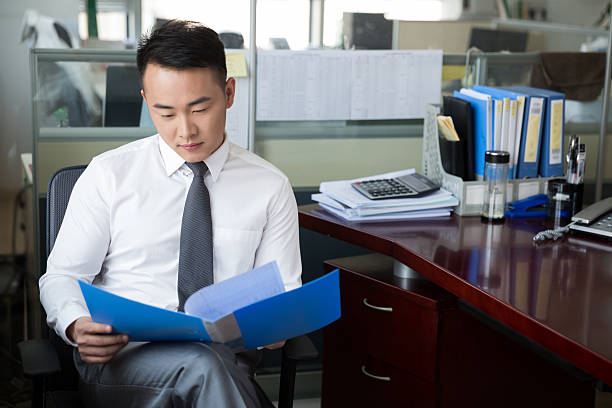 young successful man young man wearing a suit, reading documents in the company, modern office civil servant stock pictures, royalty-free photos & images