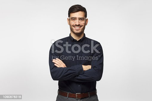 612752180istockphoto Young successful  modern business man standing with crossed arms isolated on gray background 1090878318