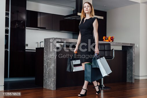 istock Young successful woman coming back home after shopping with bags 1125576523