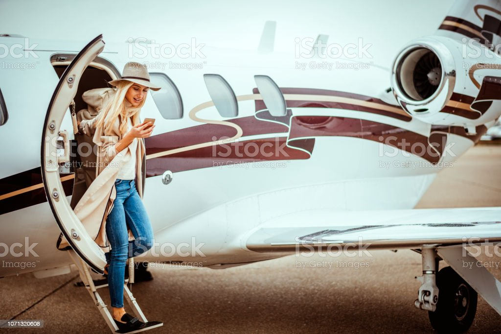 Young successful woman exiting a private airplane stock photo