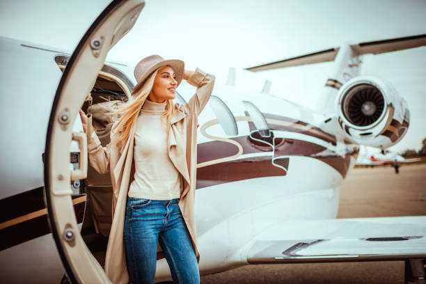 Young successful woman exiting a private airplane Young successful girl getting out of a private jet parked on a runway. She is holding her hat. status symbol stock pictures, royalty-free photos & images