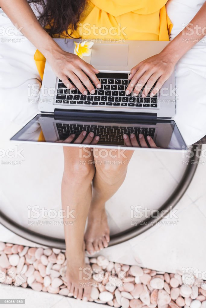 Young successful woman prints on keyboard close-up. Works as freelancer online in outdoor garden. Internet work in travel stock photo