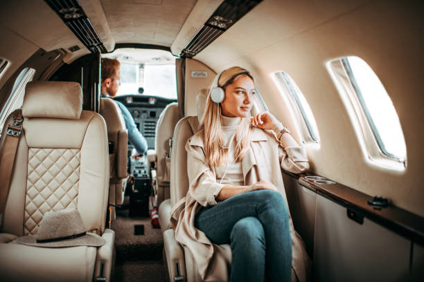 Young successful woman sitting on a private jet and listening to music through headphones stock photo