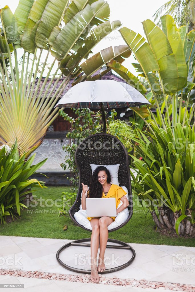 Young successful woman works as freelancer online in outdoor garden. Brunette in yellow dress with silver laptop. Internet work in travel stock photo