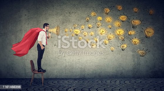 istock Young super hero businessman standing on a chair screaming in megaphpne spreading new ideas 1161466356