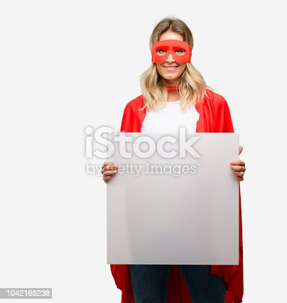 Young super hero woman wearing cape holding blank advertising banner, good poster for ad, offer or announcement, big paper billboard