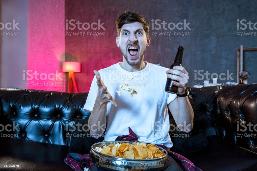 Young supporter man watching football game on television sitting stock photo