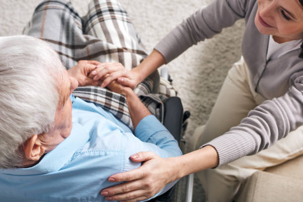 Young supportive female caregiver sitting by senior man in wheelchair stock photo