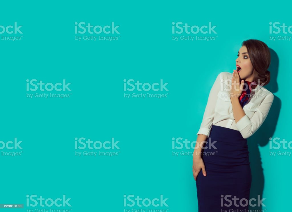 Young suprised woman looking left with her hand beside mouth. stock photo