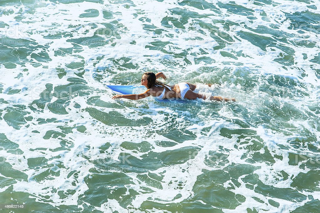 young surfer girl padding through the surf stock photo