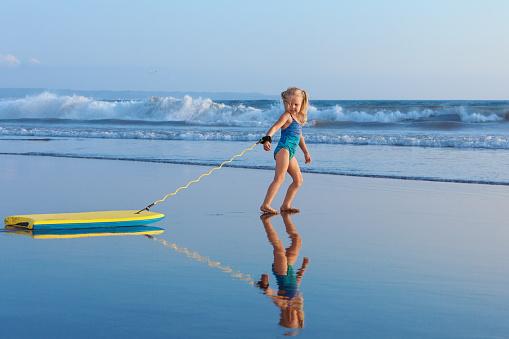 Young surfer girl with bodyboard walks along beach sea surf