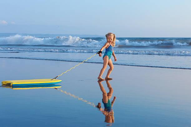 young surfer girl with bodyboard walks along beach sea surf - pool schritte stock-fotos und bilder