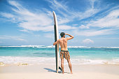 Young surfer guy  with surfboard enjoying on the beach.