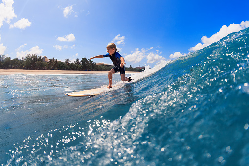 Happy surf boy - young surfer learn to ride on surfboard with fun on sea waves. Active family lifestyle, kids outdoor water sport lessons, swimming activity in surfing camp. Summer vacation with child