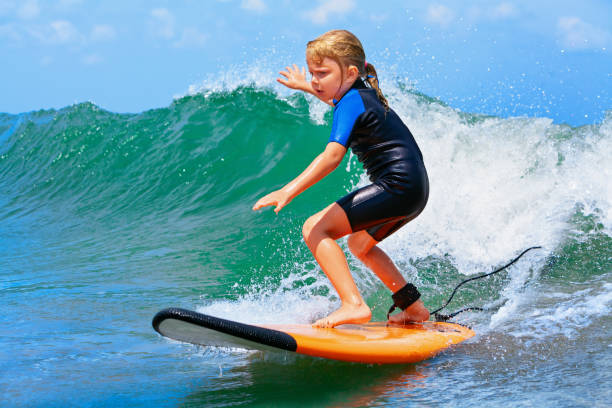 young surfer rides on surfboard with fun on sea waves - fala przybrzeżna zdjęcia i obrazy z banku zdjęć