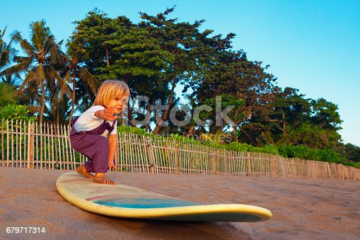 istock Young surfer stand on surfboard with fun on sunset beach 679717314