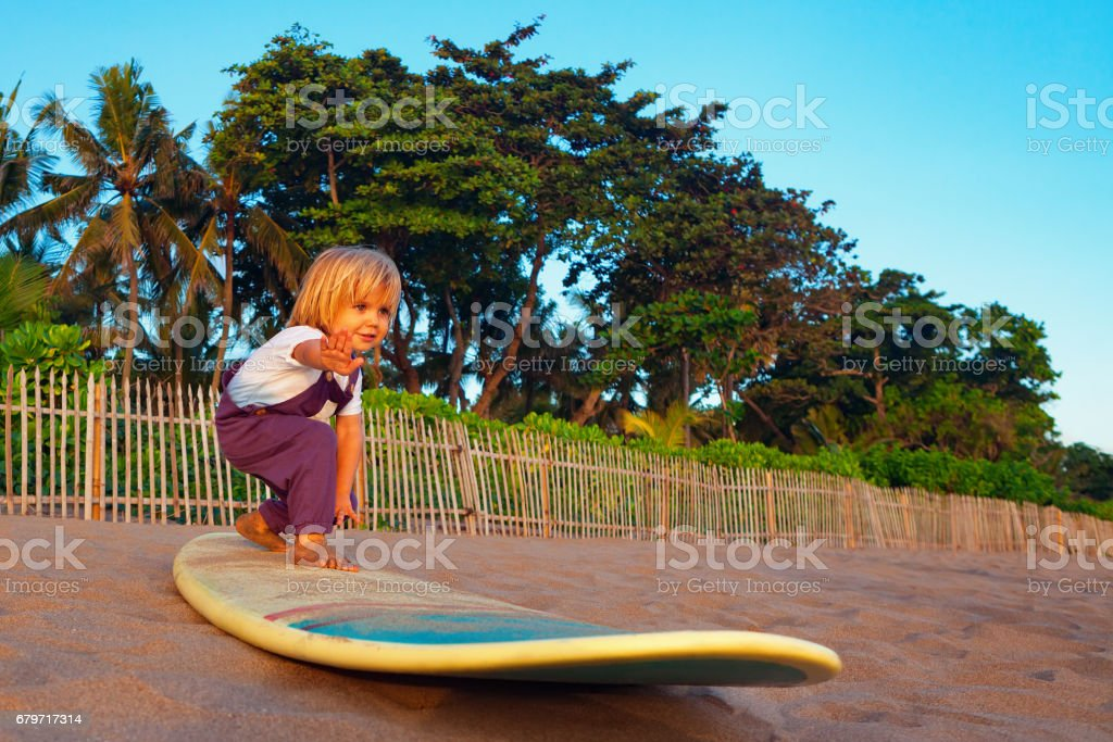 Young surfer stand on surfboard with fun on sunset beach stock photo