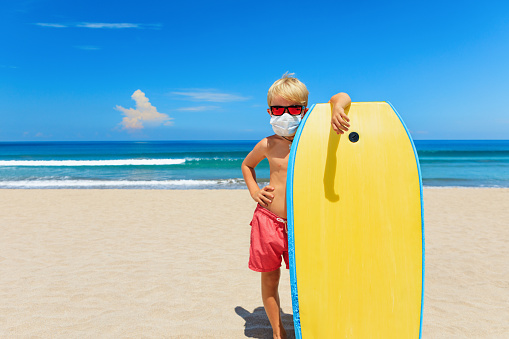 Young surfer wearing sunglasses, protective mask on sea beach