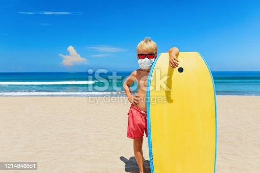 Young surfer wearing sunglasses, protective mask on sea beach with body board. Summer tours, cruises cancellation due to coronavirus COVID-19 epidemic. Safe travel destinations for family vacation.