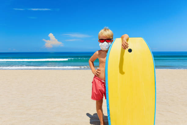 Young surfer wearing sunglasses, protective mask on sea beach Young surfer wearing sunglasses, protective mask on sea beach with body board. Summer tours, cruises cancellation due to coronavirus COVID-19 epidemic. Safe travel destinations for family vacation. lesser sunda islands stock pictures, royalty-free photos & images