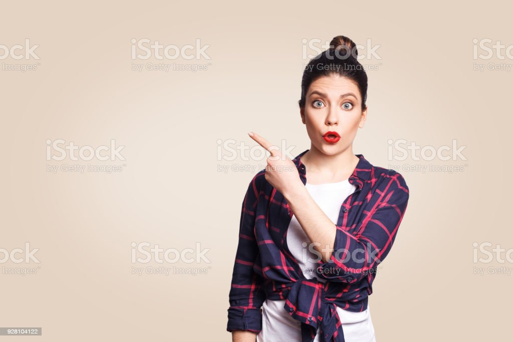 Young surprised girl with casual style and bun hair pointing her finger sideways stock photo
