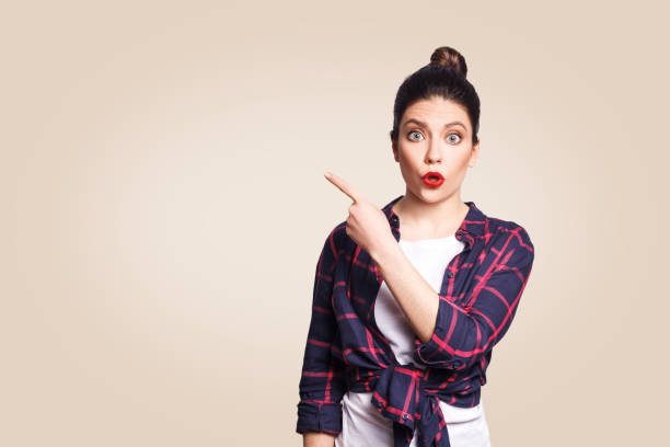 young surprised girl with casual style and bun hair pointing her finger sideways - majestic stock photos and pictures