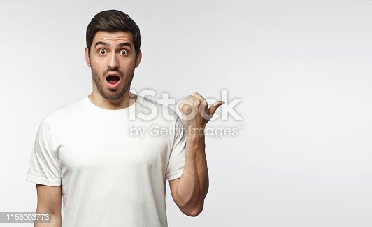 istock Young surprised man in white t-shirt looking at camera with open mouth, pointing right, copy space for ads, isolated on gray background 1153003773