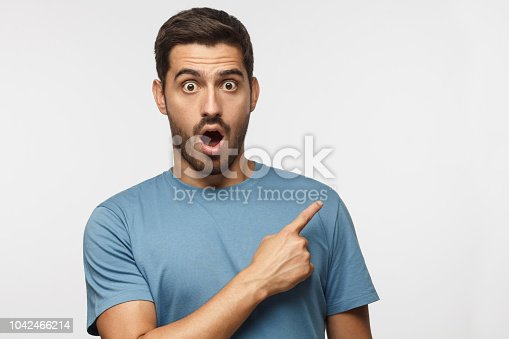 Young surprised man isolated on gray background in blue t-shirt looking at camera with open mouth, pointing right, copyspace for ads