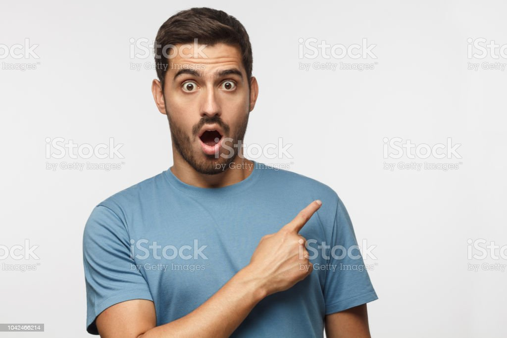 Young surprised man isolated on gray background in blue t-shirt looking at camera with open mouth, pointing right, copyspace for ads stock photo
