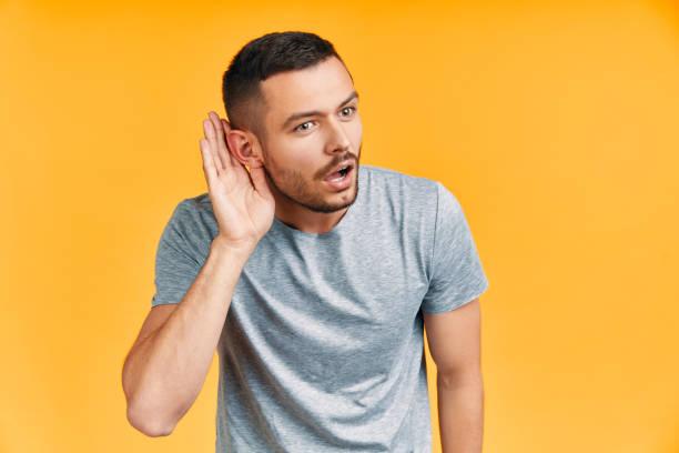 Joven sorprendido escuchando algo con cuidado y sostiene su mano cerca de la oreja sobre el fondo amarillo - foto de stock