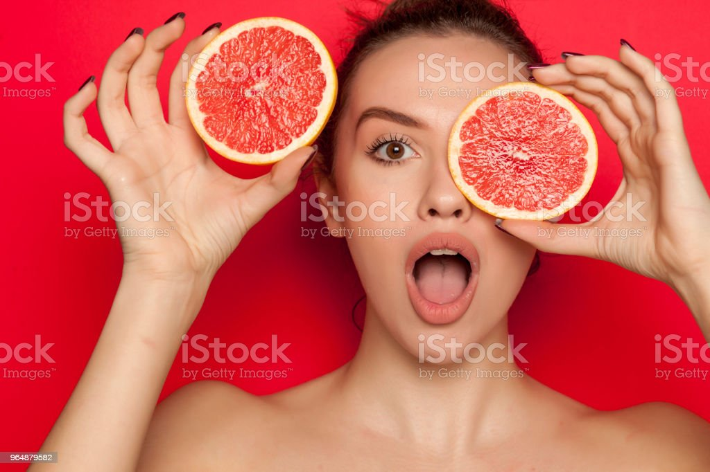 Young surprised woman posing with slices of red grapefruit on her face on red background royalty-free stock photo