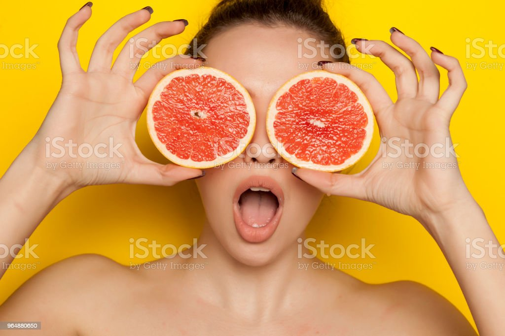 Young surprised woman posing with slices of red grapefruit on her face on yellow background royalty-free stock photo