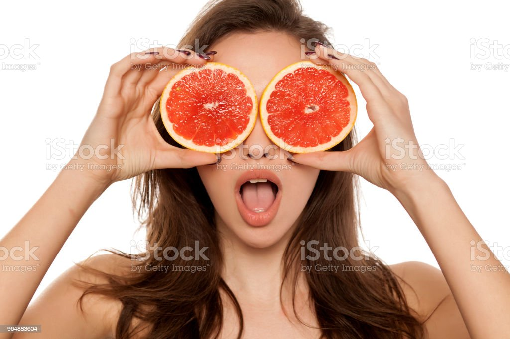 Young surprised woman posing with slices of red grapefruit on her face on white background royalty-free stock photo