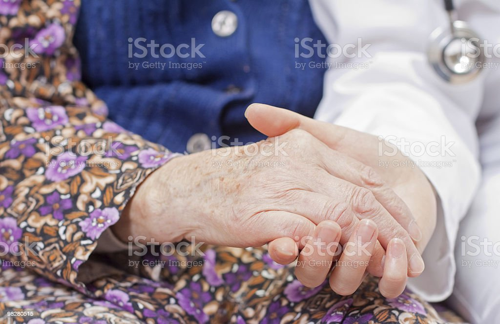 Young sweet doctor holds the old woman's hand royalty-free stock photo