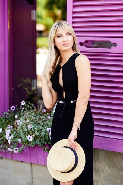 un jeune, sympathique blonde en robe noire et un chapeau de paille dans ses mains, se dresse sur l'arrière-plan d'une fenêtre avec des volets violets - cosmetique store photos et images de collection