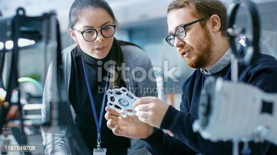 Young Talented Male and Female Engineers In a Modern Laboratory Discussing Prototype built with the Help of 3D Printer.