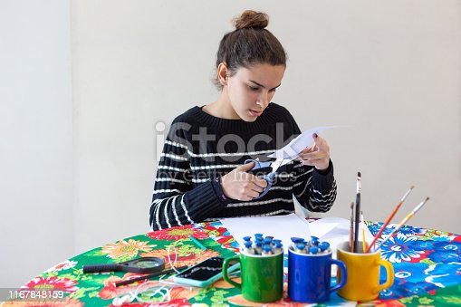 istock Young talented woman artist sitting at the table with flowered tablecloth making art with pencils, paper, scissors, magnifying glass, brush and paints in colorful mugs while listening to music on cellphone with white background. 1167848159