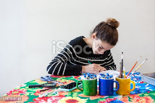 istock Young talented woman artist sitting at the table with flowered tablecloth making art with pencils, paper, scissors, magnifying glass, brush and paints in colorful mugs while listening to music on cellphone with white background. 1167848181