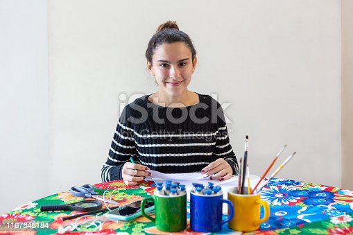 istock Young talented woman artist sitting at the table with flowered tablecloth making art with pencils, paper, scissors, magnifying glass, brush and paints in colorful mugs while listening to music on cellphone with white background. 1167848184