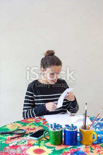 istock Young talented woman artist sitting at the table with flowered tablecloth making art with pencils, paper, scissors, magnifying glass, brush and paints in colorful mugs while listening to music on cellphone with white background. 1167848187