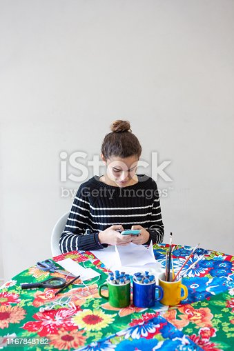istock Young talented woman artist typing message on cellphone sitting at table with flowered towel in her studio with white background. Uses pencils, paper, scissors, loupe, brush and inks on colored mugs. 1167848182
