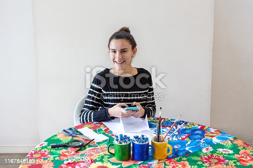 istock Young talented woman artist typing message on cellphone sitting at table with flowered towel in her studio with white background. Uses pencils, paper, scissors, loupe, brush and inks on colored mugs. 1167848183