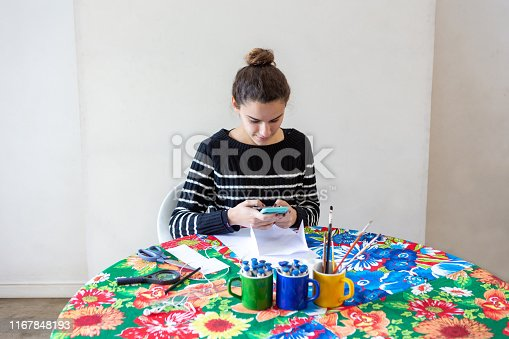 istock Young talented woman artist typing message on cellphone sitting at table with flowered towel in her studio with white background. Uses pencils, paper, scissors, loupe, brush and inks on colored mugs. 1167848193