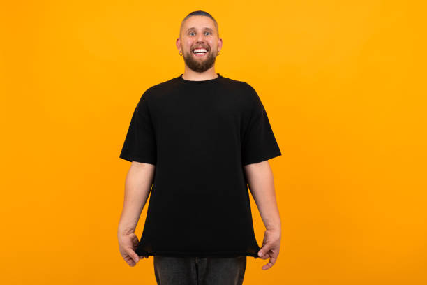 Young tall man with short black hair in black t-shirt smiles isolated on orange background stock photo