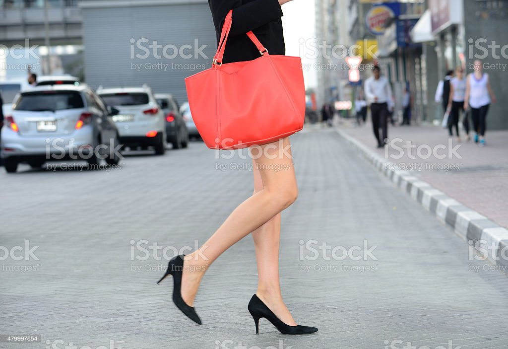 Young tall woman with red bag crossing Dubai street stock photo