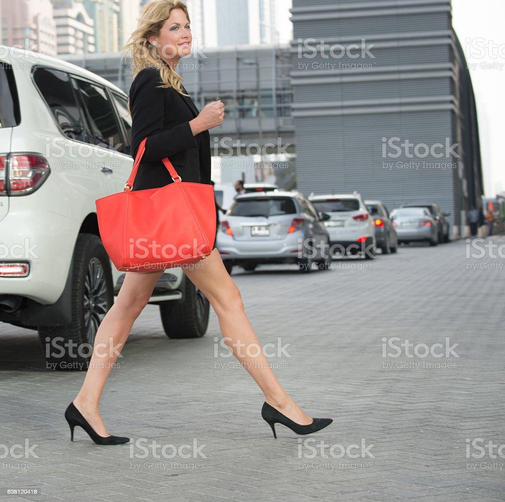 Junge Gerade Frau mit roten Tasche crossing Dubai street – Foto