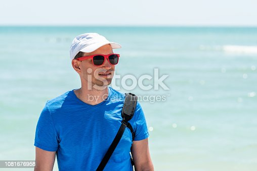 istock Young tan man hipster millennial happy smiling face closeup on beach during sunny day with red sunglasses in Sanibel Island, Florida with ocean, gulf of Mexico 1081676958