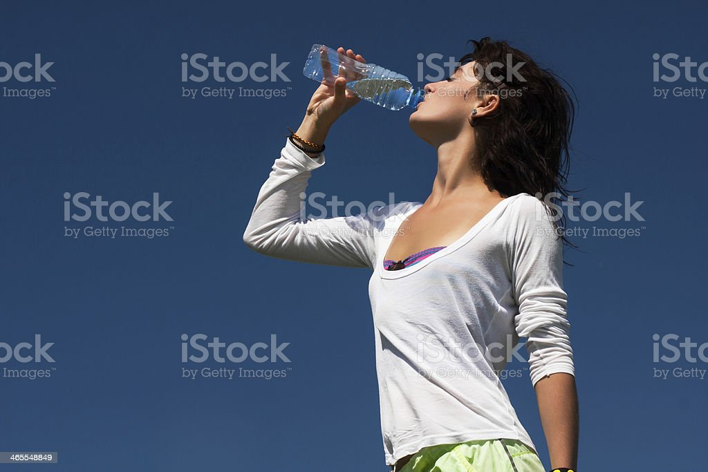 Young tanned athlete drinking water royalty-free stock photo