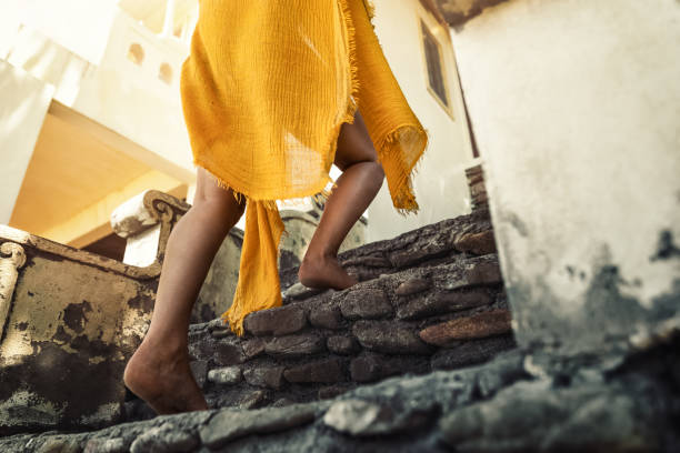 Junge braungebrannte Frau Schritte im Obergeschoss in einem wunderschönen Bademode-Strand Kleid - Beine und Füße – Foto