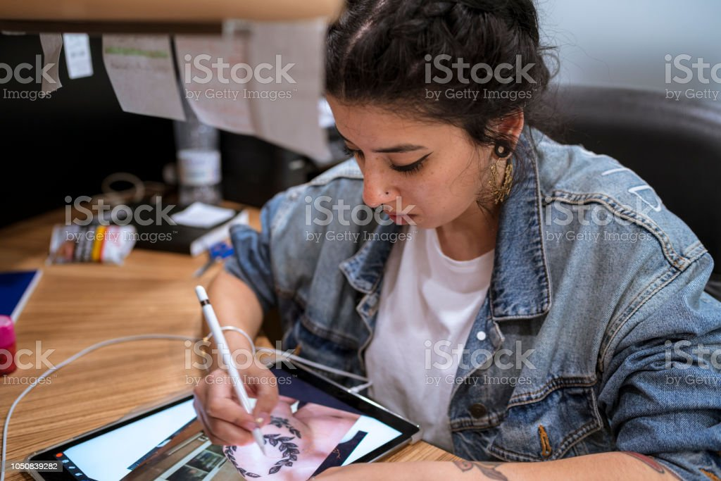 Young tattoo artist drawing her new design on the tablet. стоковое фото